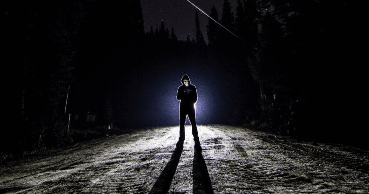 Dude in black pants and black hoodie standing in front of headlights in what appears to be the middle of nowhere.